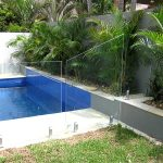 Glass Pool Fence next to a swimming pool