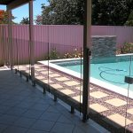 Frameless glass design next to pavers and pool
